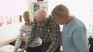 Heidi Grönmark och Eva Lindgren hjälper Robin Hackman