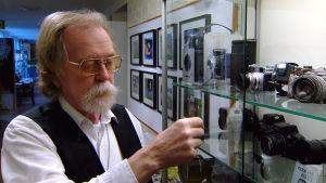 Man med kamera i handen vid museimonter