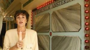 Toimittaja Raija Massala spiikkaa Amsterdamin seksimuseon tekopenis kädessään.