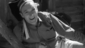 Näyttelijä Börje Lampenius laulaa lapinhatussa ja shortseissa.