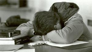 opiskelija nukkuu pöytään vasten tunnilla