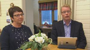 Kvinna och man sitter vid ett mötesbord med en dator uppslagen framför sig.
