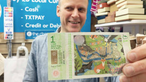 Köpmannen Andy förevisar en Bristolpund-sedel.