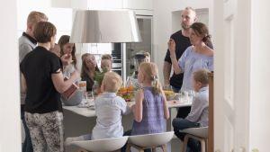 Familjer med barn runt ett matbord.