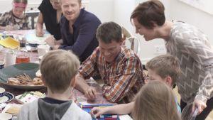 Vuxna och barn pysslar vid matbordet.
