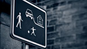 Trafikmärke med barn som leker på gårdsplan.