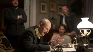 Kung Haakon (Jesper Christensen) sitter vid ett skrivbord och förklarar sitt beslut.