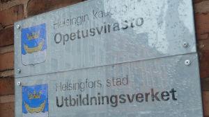En regnvåt skylt där det står Helsingfors stad Utbildningsverket.