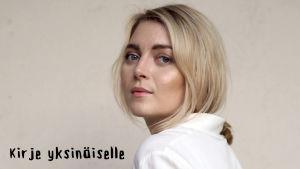 Jenni Rotonen katsoo vaaleasävyisessä kuvassa sivuttain kameraan.