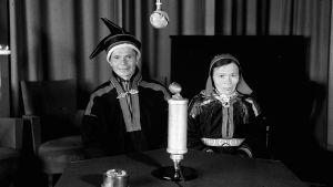 Saamelaispukuiset mies ja nainen istuvat radion studiopöydän takana.