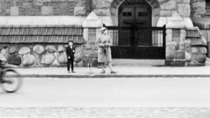 Kameraa pitelevä nainen ja poika seisovat jalkakäytävällä tähyillen ympärilleen.