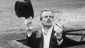 Frakkiin ja silinteriin pukeutunut mies kurkistaa viemärikaivosta.