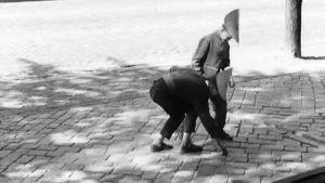 Kaksi pahvihattuista poikaa yrittää irrottaa katuun liimattua seteliä ohjelmassa Rahaa.