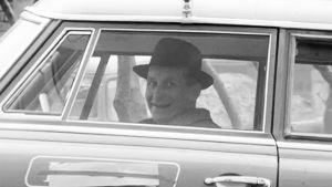 Hattupäinen istuu henkilöautossa ja hymyilee kameralle.