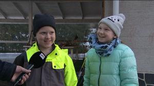 Pojke och flicka intervjuas på skolgård