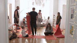Familjerna Helenius och Lindberg jogar i vardagsrummet.