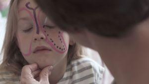 En liten flicka får en ansiktsmålning.