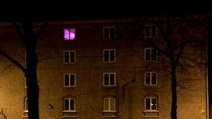 kerrostalo, yhdessä ikkunassa valo