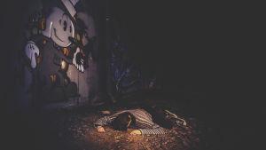 mies makaa maassa graffitiseinän edessä