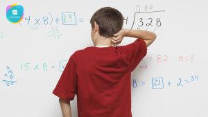 Pojke står framför krittavla med matematiska formler.