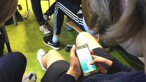 En högstadieelev som spelar på mobilen.