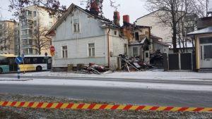 Taket på huset på Itsenäisyydenkatu har rasat ihop och förkolnade träbitar är lutade mot huset.