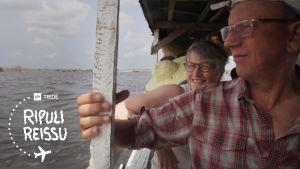 Helena ja Paavo ihailevat maisemia veneestä.