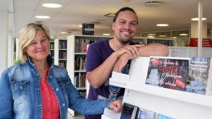 """Regina Ekblom och Benjamin Lundin står vid en hylla med cd-skivor. På en hylla står en affisch där det står """"Så överlever du zombieapokalypsen""""."""
