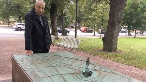 En man vid en staty som föreställer gamla åbo