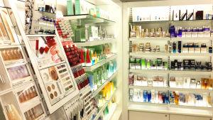 Olika kosmetiska produkter på belysta hyllor.