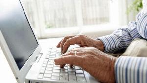 En äldre person sitter och skriver på dator.