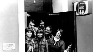 Sex personer tittar ut genom en dörr.