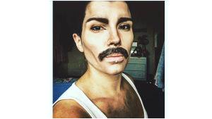 Sanna sminkad och utklädd så att hon liknar Freddie Mercury. Hon har mustasch och ett vitt linne.