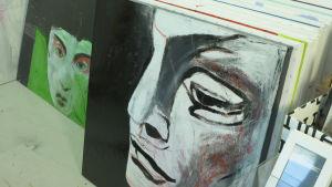 målningar radade på golvet i ett galleri