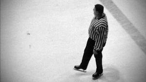 Erotuomari seuraa jääkiekko-ottelua.