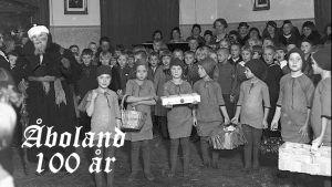 en gammal bild med julgubbe och barn som är utklädda till tomtar