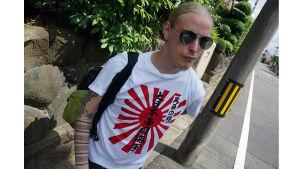 En man med långt blont hår. Han bär solglasögon och en t-shirt med med japansk text på.