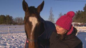Kvinna håller häst i grimman utomhus