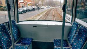 raitiovaunun tyhjiä penkkejä ja näkymä takaikunasta ulos