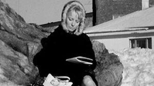 Nainen lukee lehteä ulkona