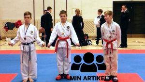 Tre taekwondokillar står bredvid varandra. Arseny Ignatiev i mitten.