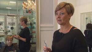 Kvinnlig frisör framför spegel i frisörsalong.