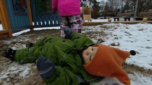 Pieni lapsi maksaa lumisessa maassa