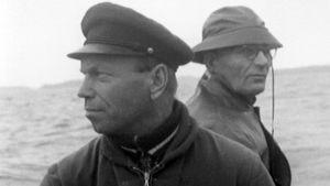 Kaksi miestä istuu veneessä.
