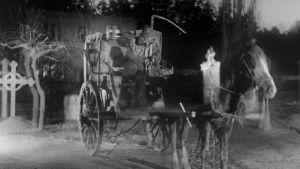 Viikatemies ajaa hevosvaunuja. Kuva Victor Sjöströmin elokuvasta Ajomies (1921)