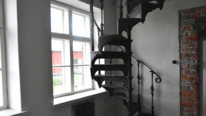 En gammal svartmålad spiraltrappa går upp i en renoverat hus.