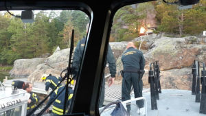 Män i overaller där det står gränsbevakningsväsendet på ryggen. De släcker en brinnande byggnad. De står på en brygga vid klippor.