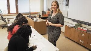 Opettaja Sanna Etelämäki katsoo kameraan ja neuvoo oppilaitaan.
