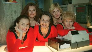 Viisi punaisiin vaatteisiin pukeutunutta naista nojaa kassaan ja hymyilee kameralle.