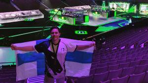 En man står inne i en stor arena. Han håller i en stor Finlands flagga. Ljuset på honom är lila. I bakgrunden syns stora skärmar och ett område för dataspelare.